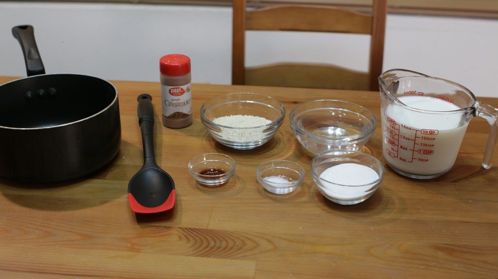 Several ingredients in glass bowls on a wooden table for  making rice pudding.