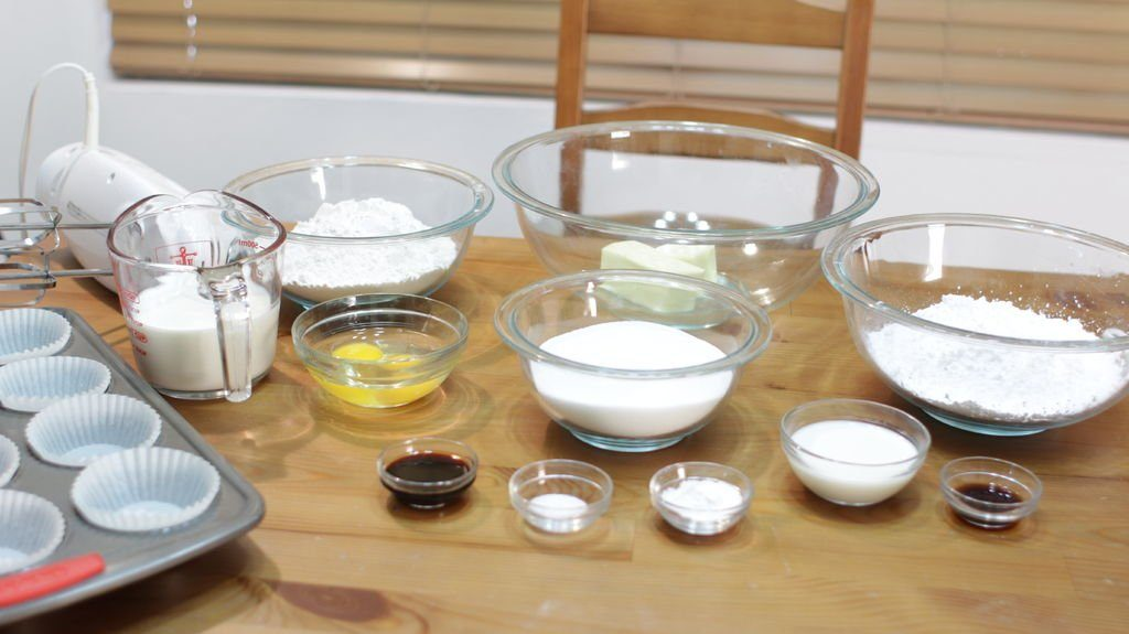 Several glass bowls holding ingredients laying on a wooden table.
