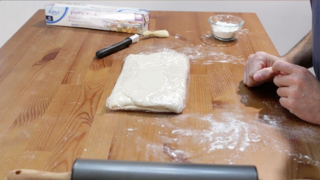 Homemade croissant dough wrapped in plastic wrap sitting on a brown wooden table.