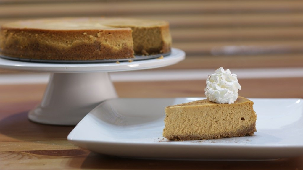 Easy pumpkin cheesecake topped with whipped cream sitting on a white plate.
