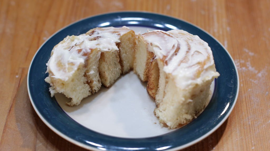 No knead cinnamon roll covered in cream cheese frosting on a green rimmed plate.
