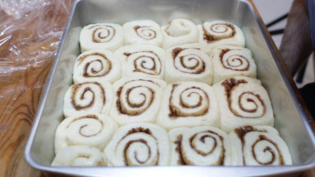homemade no knead cinnamon rolls in a large silver baking pan.