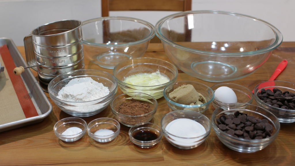 An assortment of glass bowls holding ingredients for making chocolate cookies.