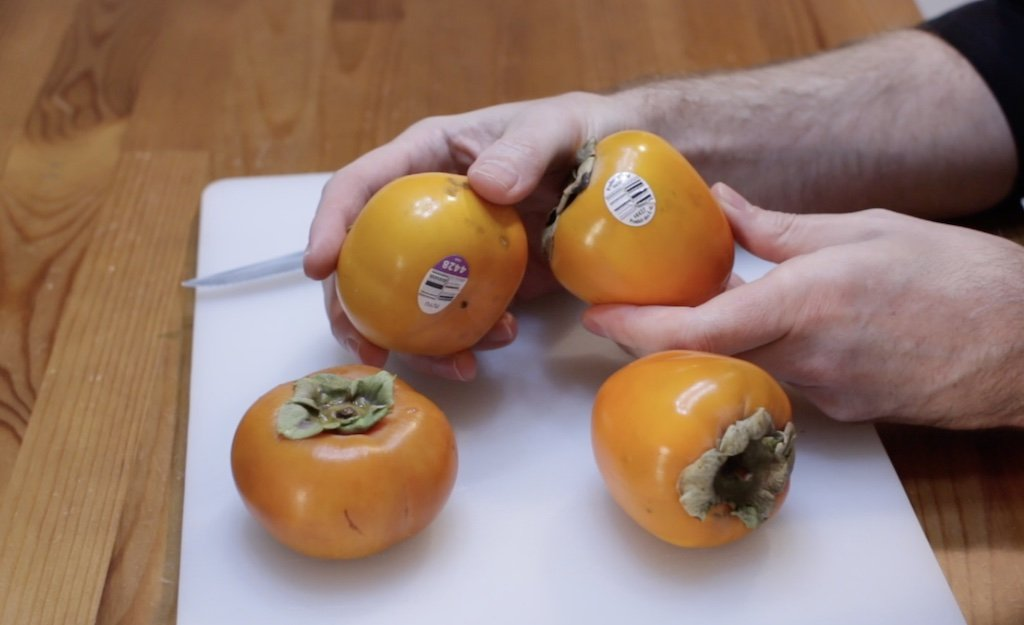 Hands holding Hachiya and Fuyu persimmons on a white cutting board