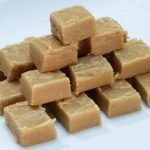 Peanut butter fudge cut in cubes stacked on a white plate
