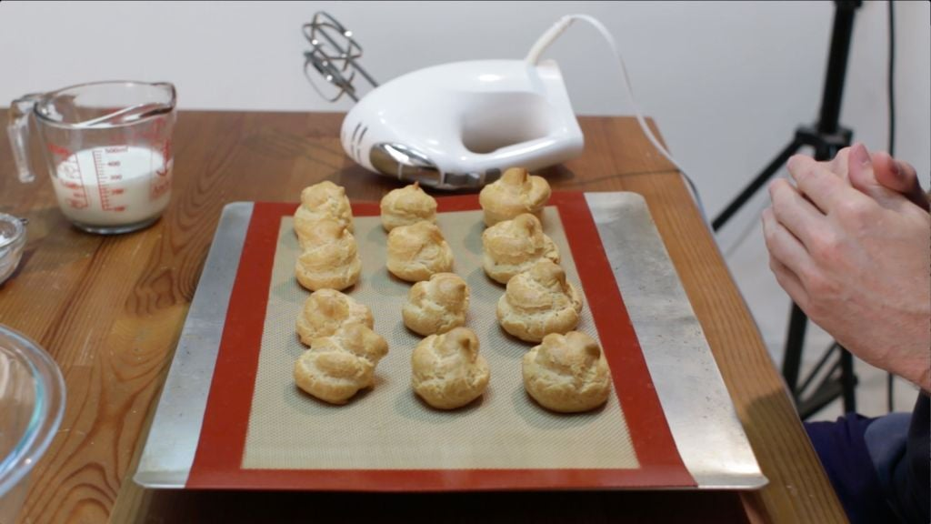 Freshly baked cream puffs resting on a silicone-mat lined cookie sheet on a table.