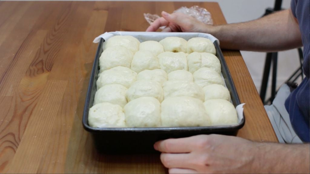 Pan of unbaked homemade dinner rolls on top of a wooden table
