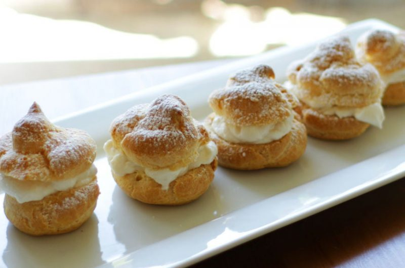 Easy homemade cream puffs sitting on a white plate