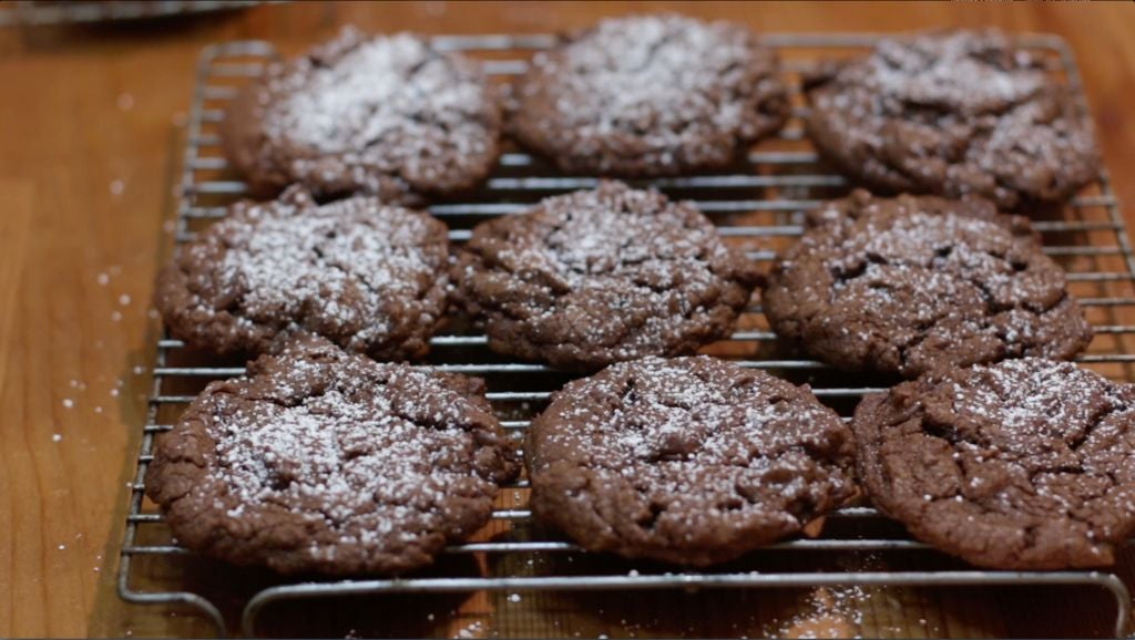 Freshly baked chocolate cookies sitting on a cookie rack on a wooden table