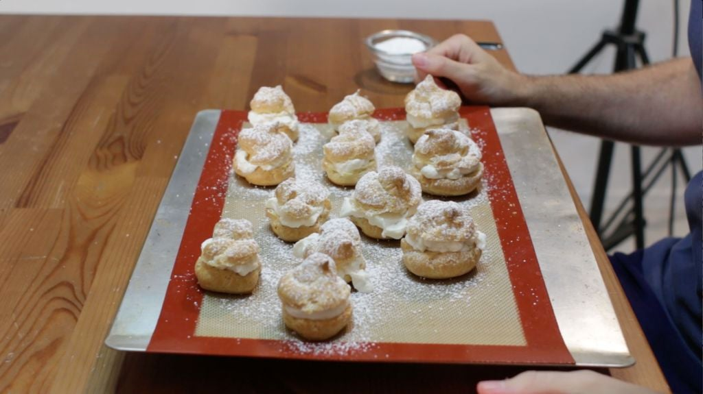 12 finished cream puffs topped with powder sugar on a silicone mat lined cookie pan.