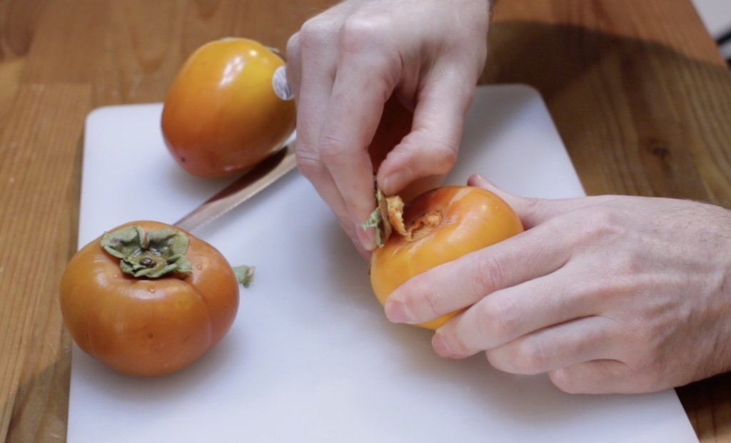 Hand removes the stem from a persimmon on a white cutting board