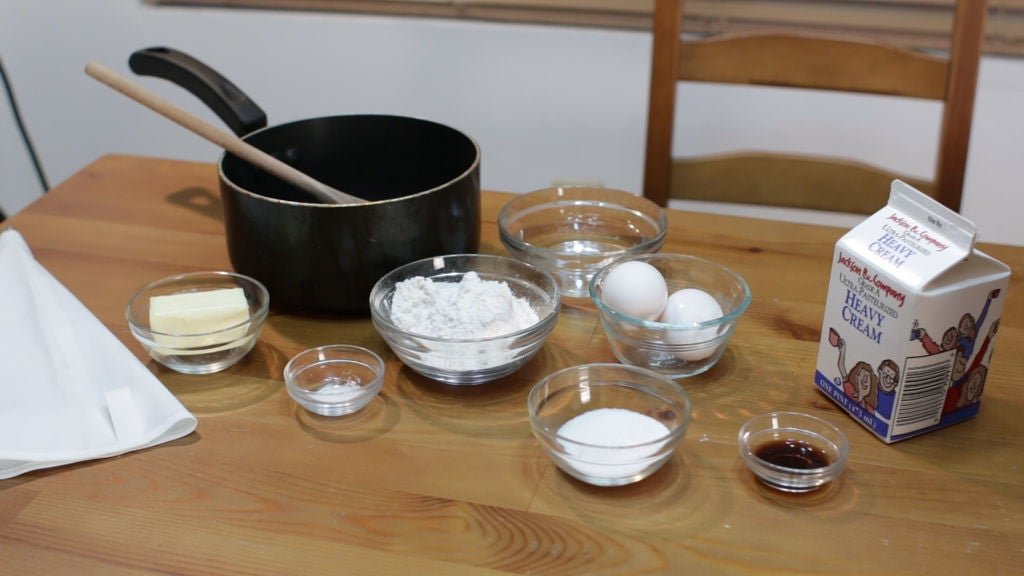 tools and ingredients needed to make the easy cream puffs recipe, eggs, flour, etc. on a wooden table.