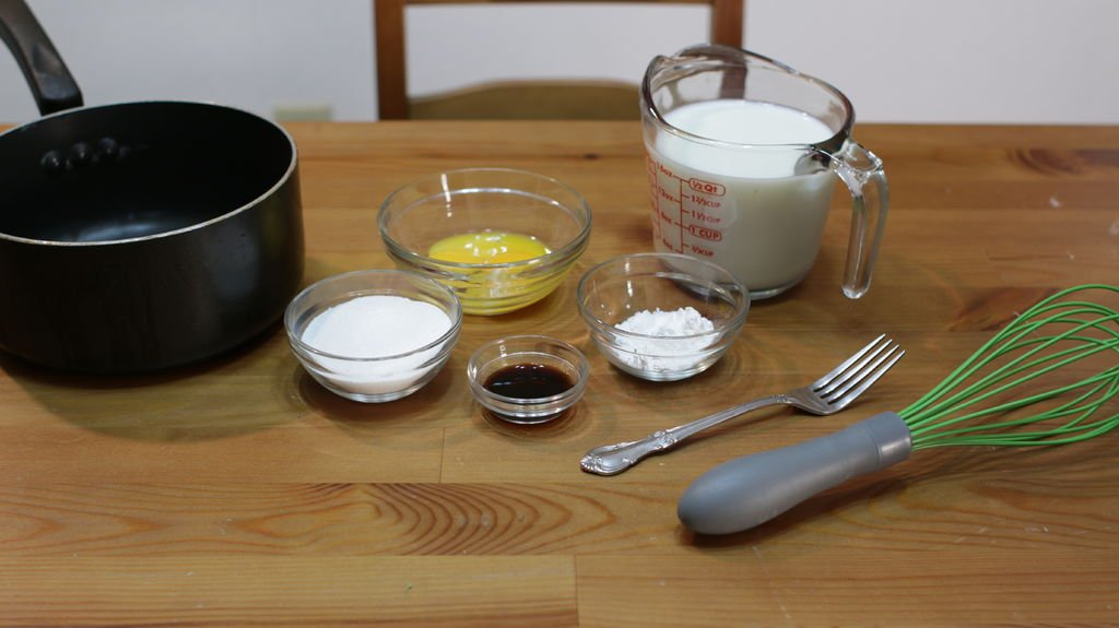 ingredients and tools to make egg custard sitting on a wooden table.