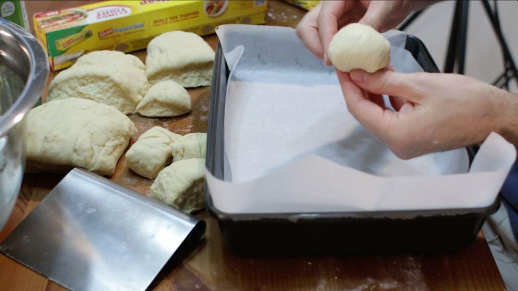 Hand rolling a ball of dinner roll dough.