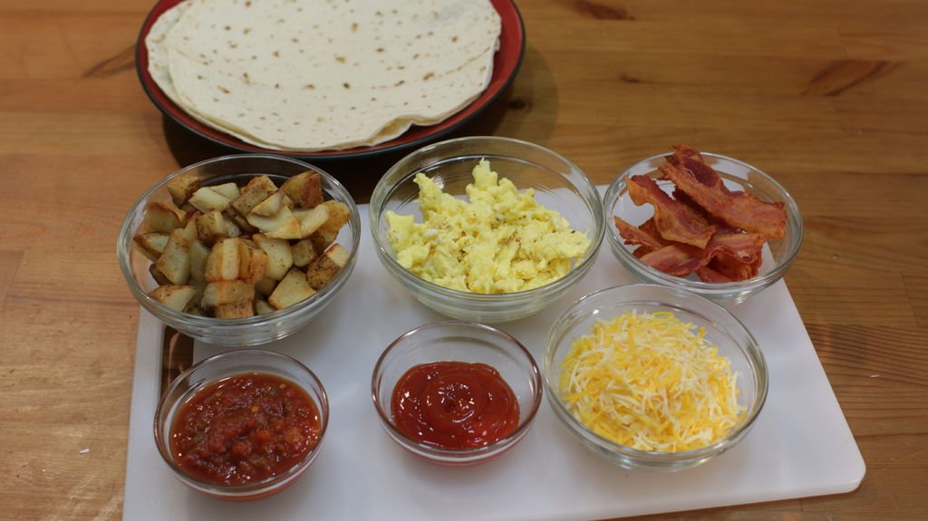 Breakfast burrito ingredients including tortillas, potatoes, eggs, bacon, cheese, salsa, and ketchup.