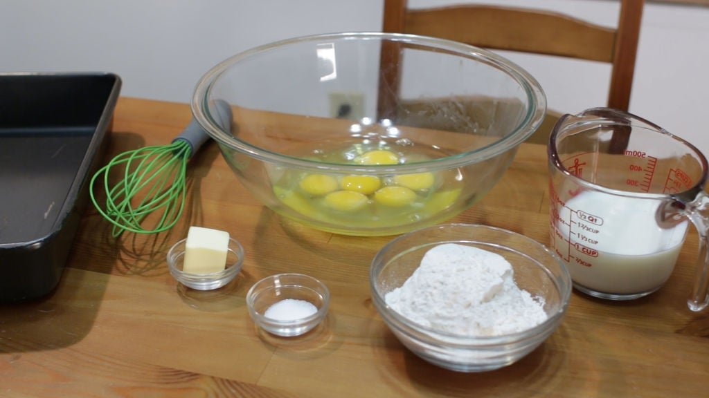 Ingredients and tools for German pancakes, whisk, eggs, milk, flour, butter, salt.