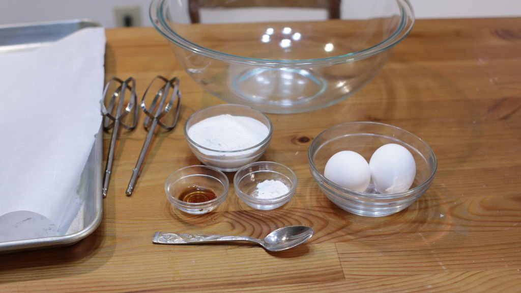 Glass bowls full of ingredients to make meringue cookies. Eggs, cream of tartar, vanilla extract, and superfine sugar.