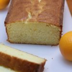 Orange cake on a white cutting board with oranges
