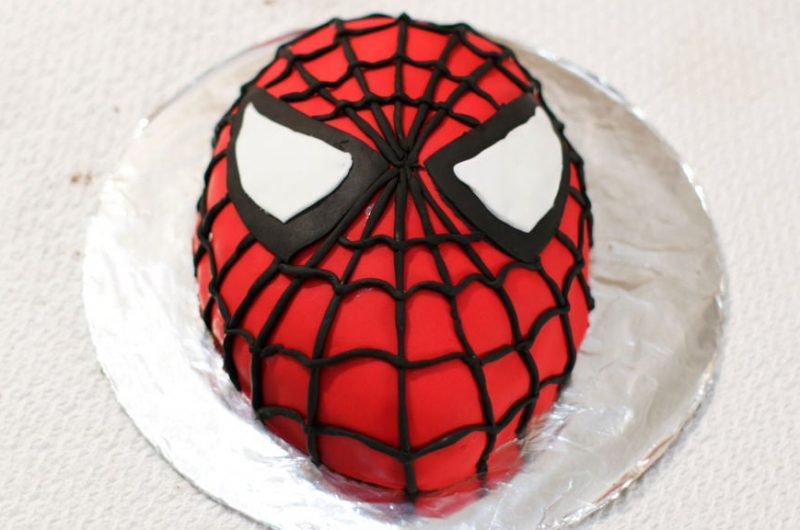 Spiderman cake on a cake board sitting on a white tablecloth