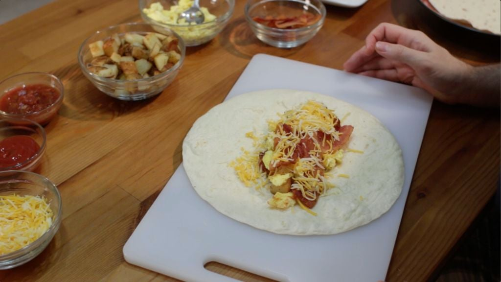 Unrolled breakfast burrito on a white cutting board on a wooden table.