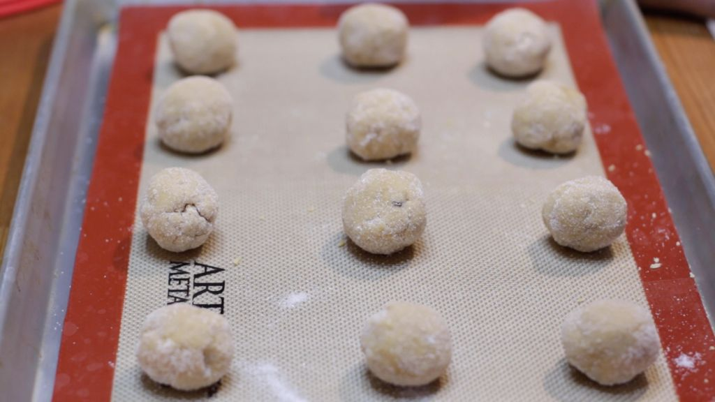 Balls of peanut butter cookie dough on a sheet pan lined with a silicone mat.