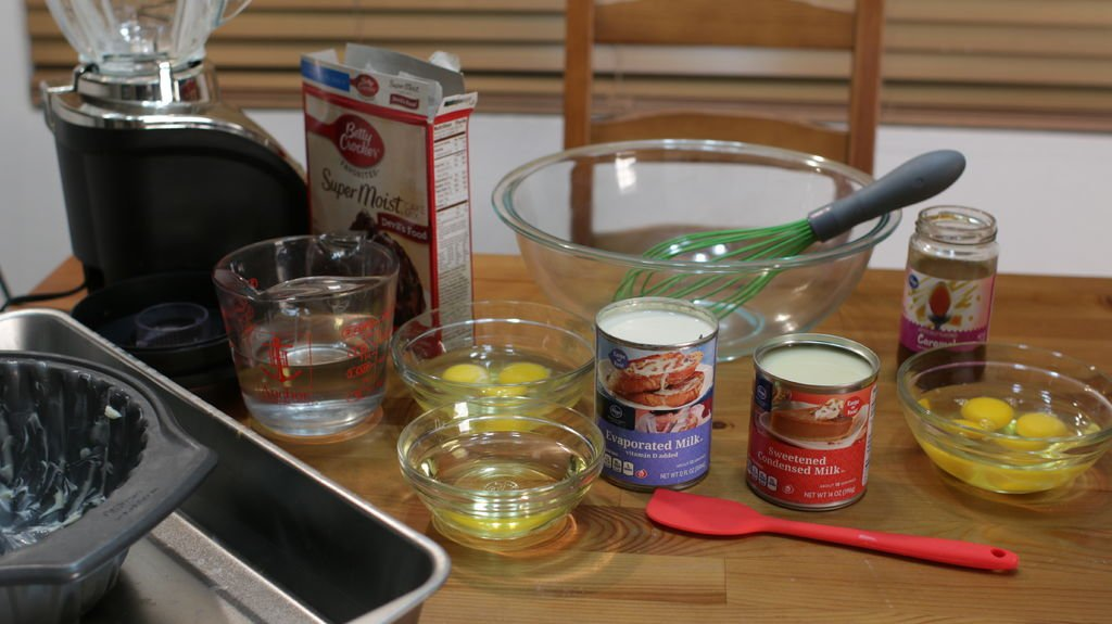 Tools and ingredients to make chocoflan. Eggs, milk, caramel, water, cake mix, etc.