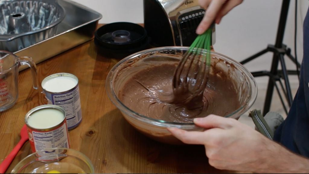 Finishing the chocoflan cake base with a chocolate cake mix in a large bowl on top of a wooden table.