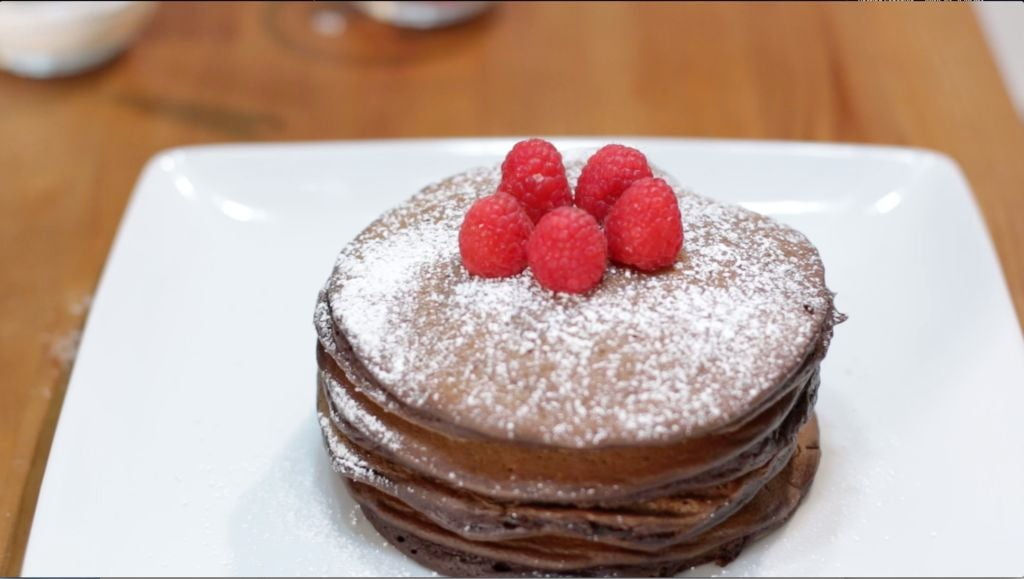 Homemade chocolate pancakes topped with powdered sugar and raspberries.