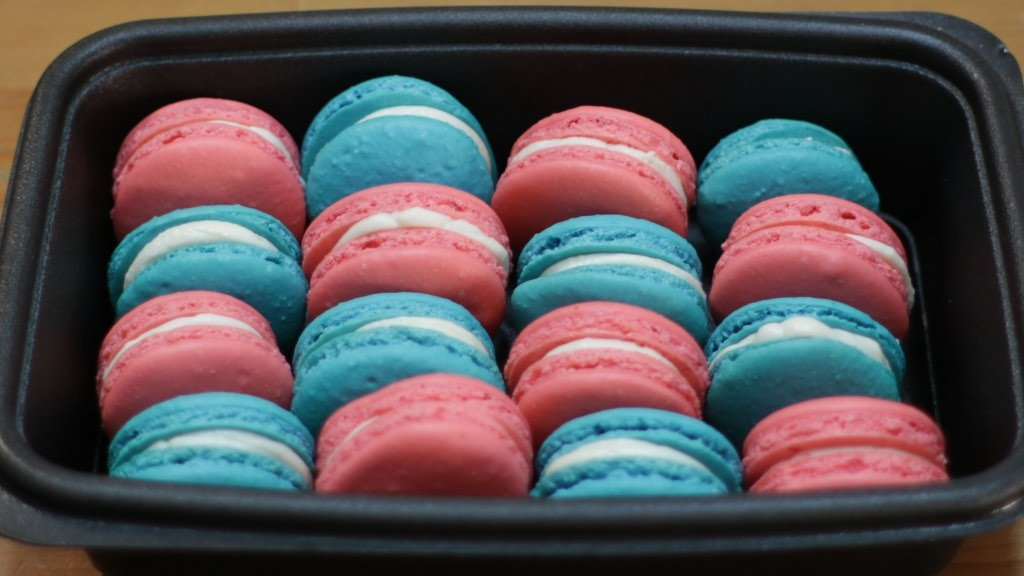 a black container filled with blue and pink classic French macarons