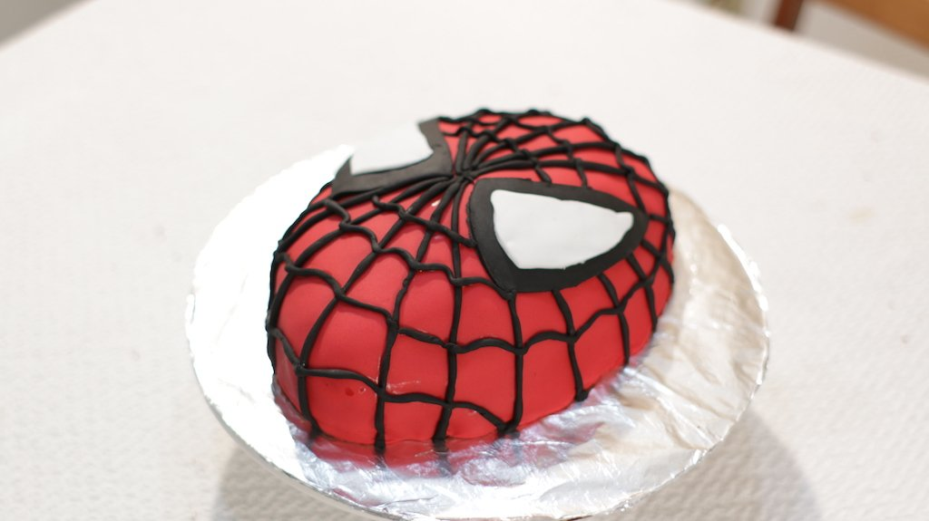 Finished homemade Spiderman cake on a cake board on top of cake pedestal.