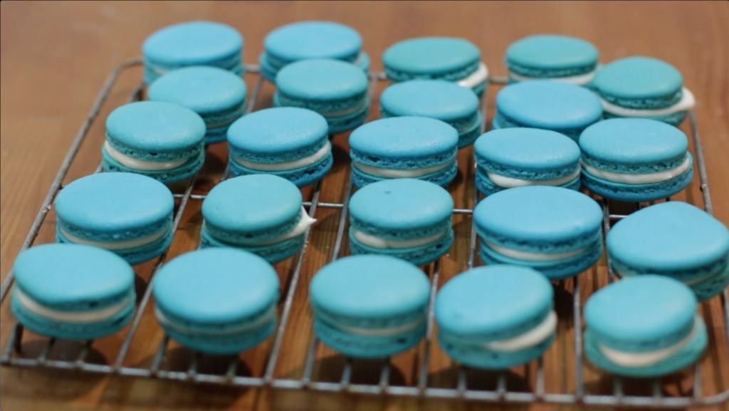 Several blue French macarons sitting on a wire rack on a wooden table.