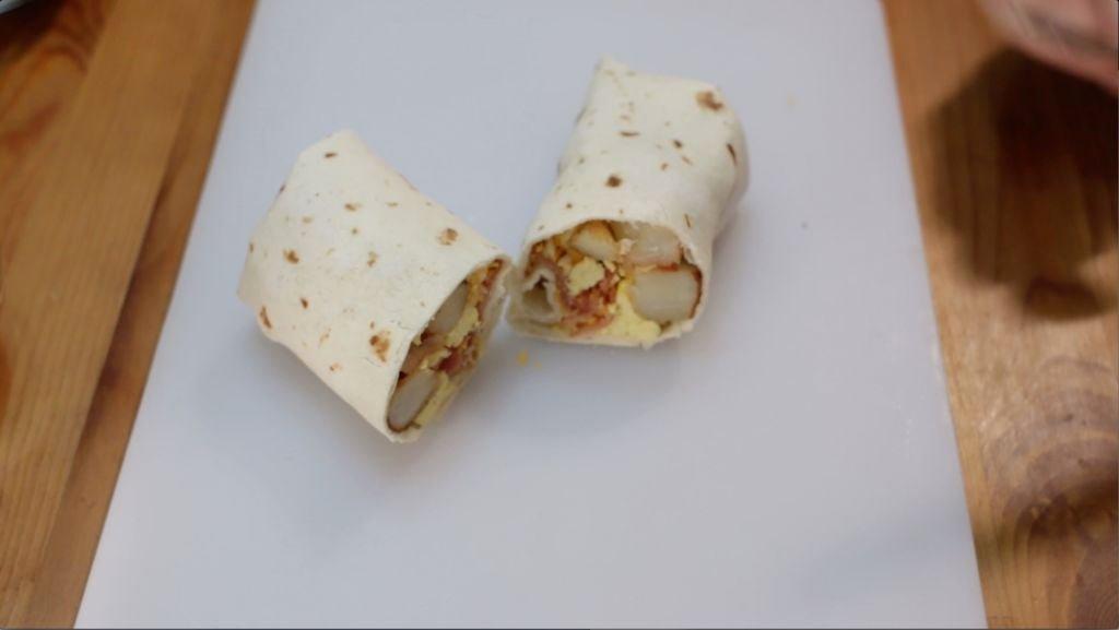 Finished breakfast burrito cut in half sitting on a white cutting board