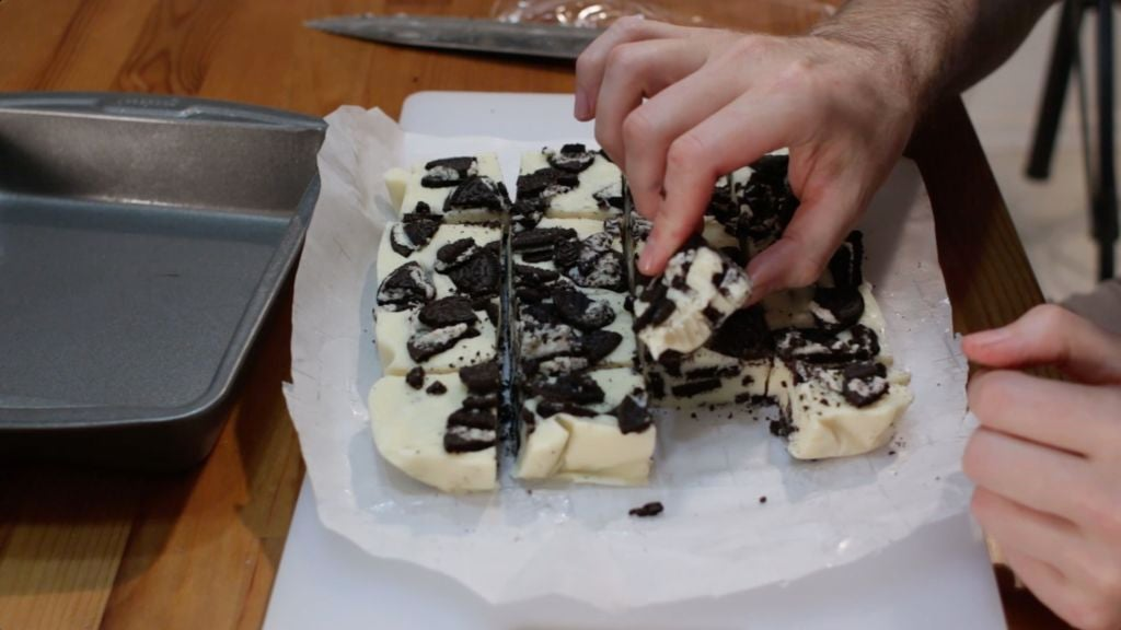 Hand holding a piece of cookies and cream fudge.