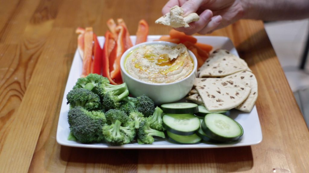 White bowl of hummus on a white plate of raw veggies and pita bread