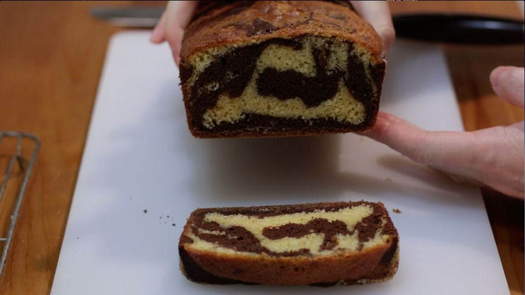 Hand holding a marble cake that has been sliced.