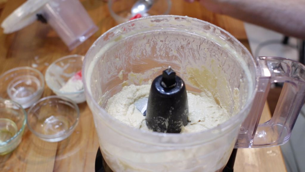 Blended hummus in a food processor on a wooden table