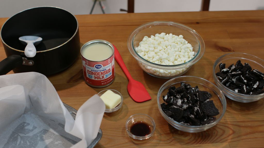 Ingredients and tools for making cookies and cream fudge in glass bowls on a wooden table, including white chocolate, Oreo cookies, butter, etc.