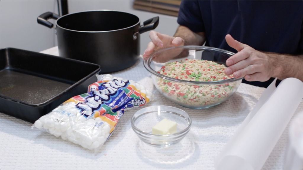 Large bowl full of Rice Krispies cereal along with marshmallows and butter and a large pot on a table.