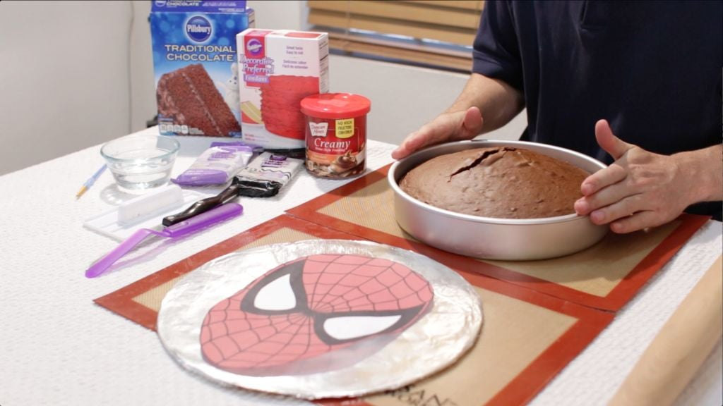 Baked cake in a pan with a Spiderman face template, frosting, and fondant.