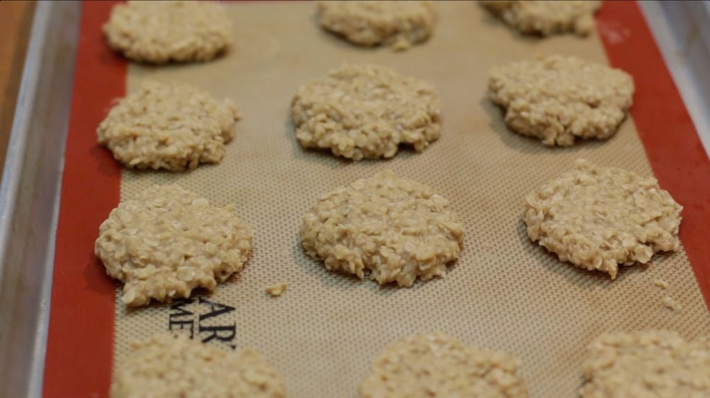 Finished no-bake peanut butter cookies on a pan lined with a silicone mat.