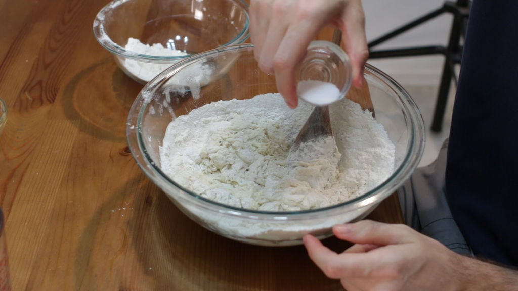 adding flour, olive oil, and salt to the Italian bread dough