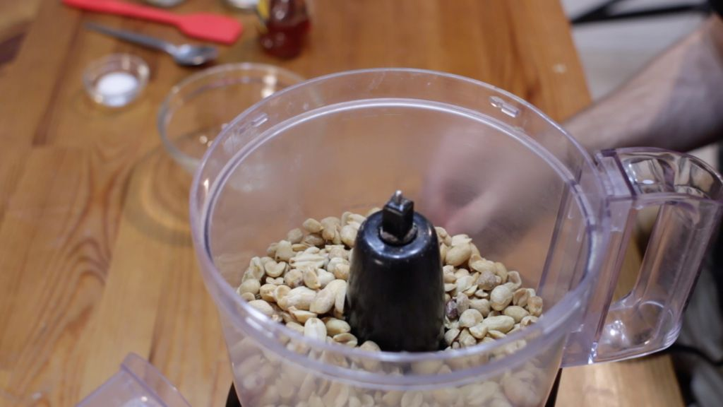 dry roasted peanuts in a food processor on a wooden table