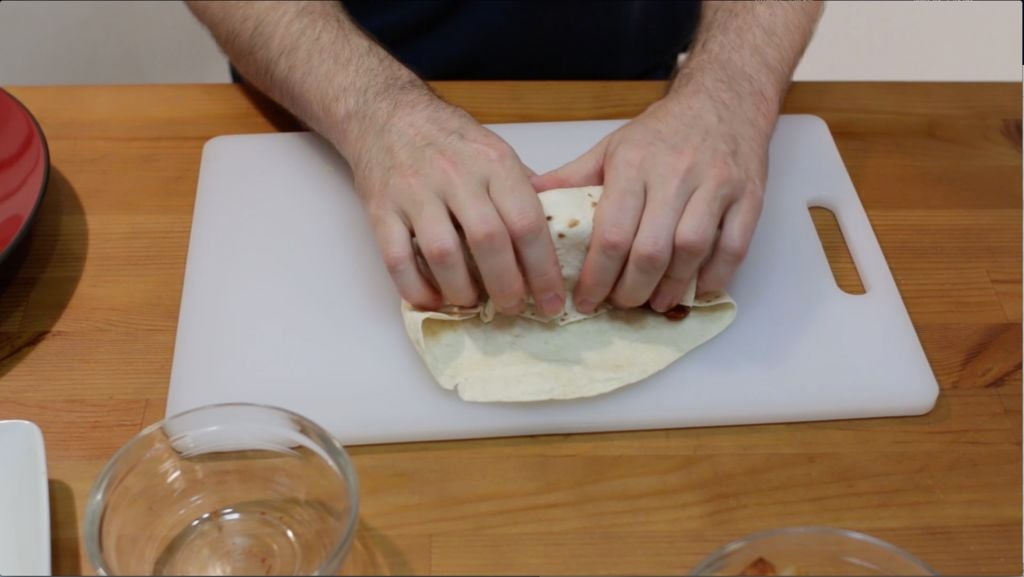 Hands rolling a breakfast burrito on a white cutting board