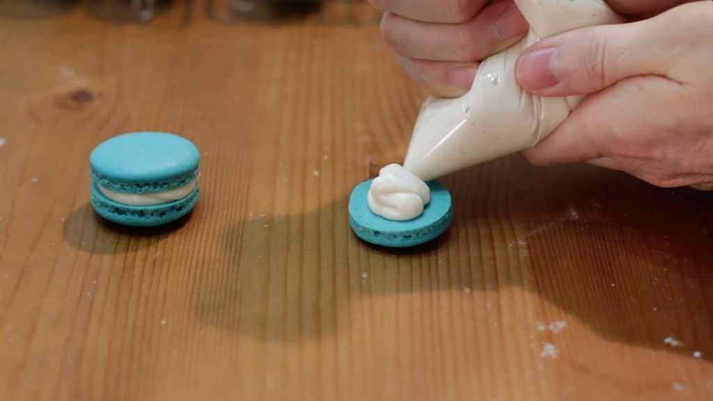 Piping buttercream frosting onto the back of a macaron shell