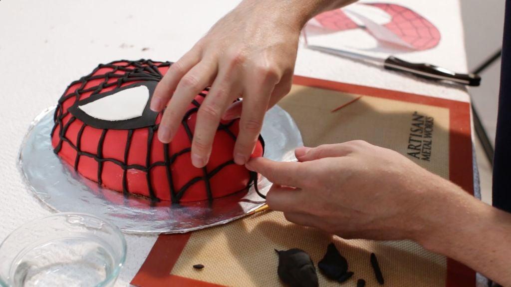 Hands placing black fondant webbing on the Spiderman cake head.