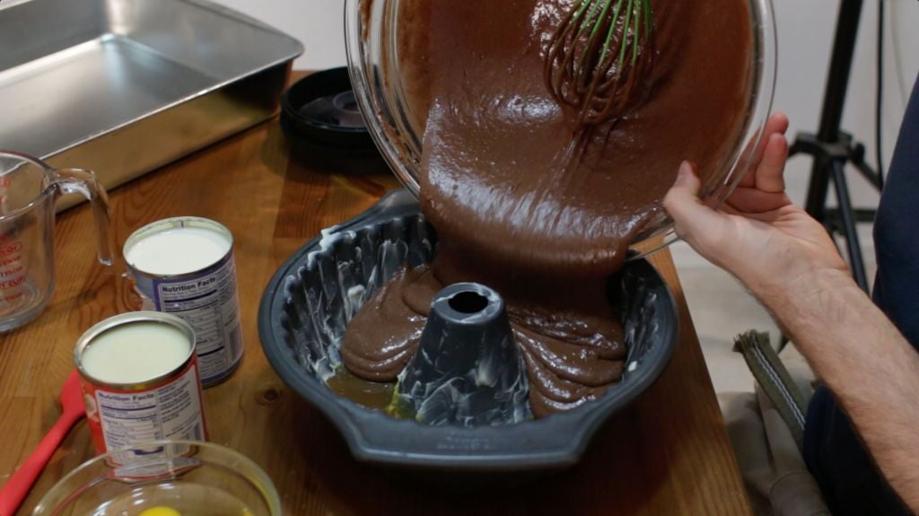 Pouring the chocolate cake batter over the caramel in a bundt cake pan.