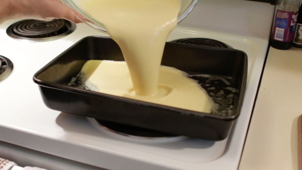 Hand pouring a glass bowl of dutch baby batter into a pan.
