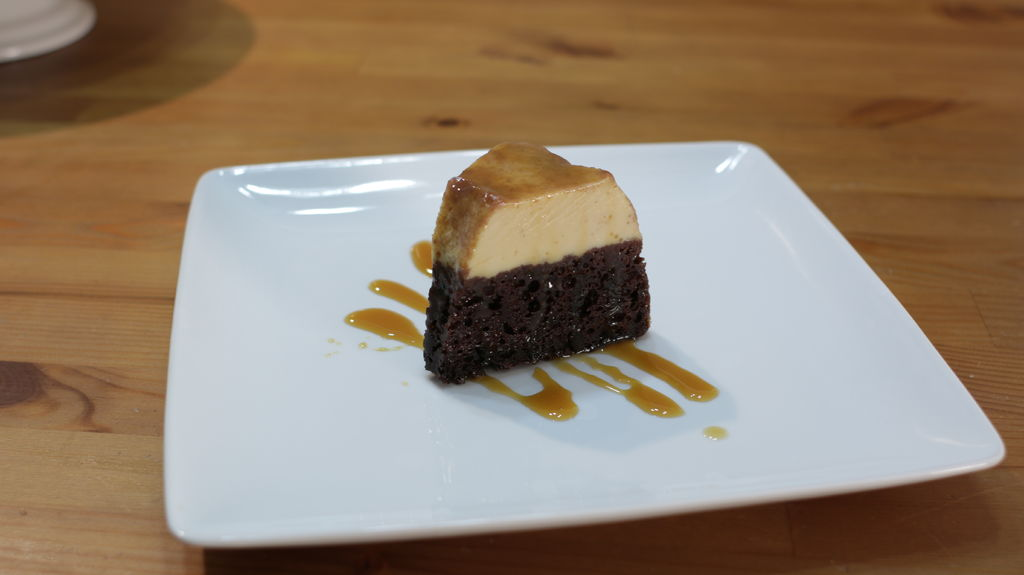 Slice of chocoflan on a white plate on a wooden table.