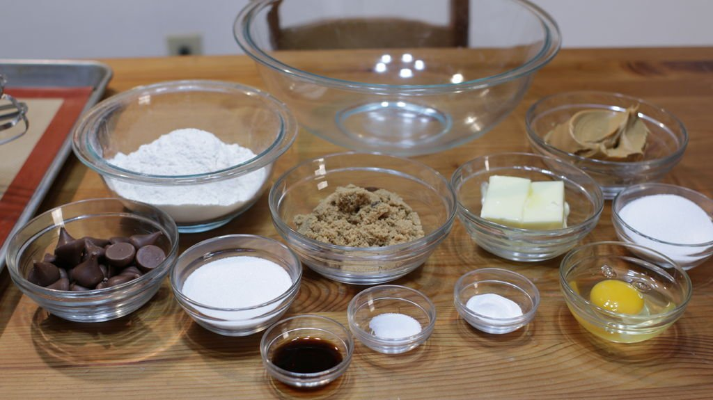 Ingredients and tools to make peanut butter blossoms, sugar, egg, vanilla, Hershey's kisses, flour, butter, etc. in glass bowls on top a wooden table.