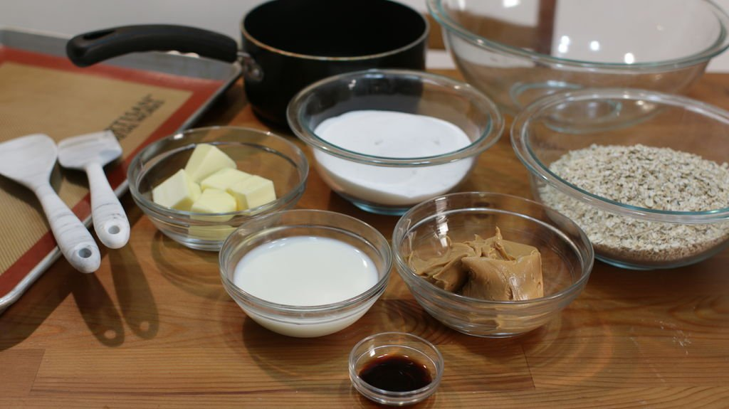 Tools and ingredients to make no-bake peanut butter cookies including butter, sugar, milk, peanut butter and oats all in glass bowls sitting on a wooden table.